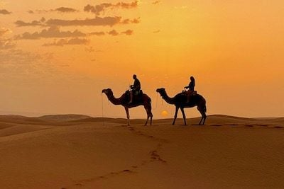 A couple takes a sunset camel ride in the distant sand dunes of Erg Chigaga in Morocco after the road ends at Zagora and Mhamid on a sustainable tour in Morocco
